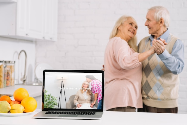 Grandparents behind laptop mockup
