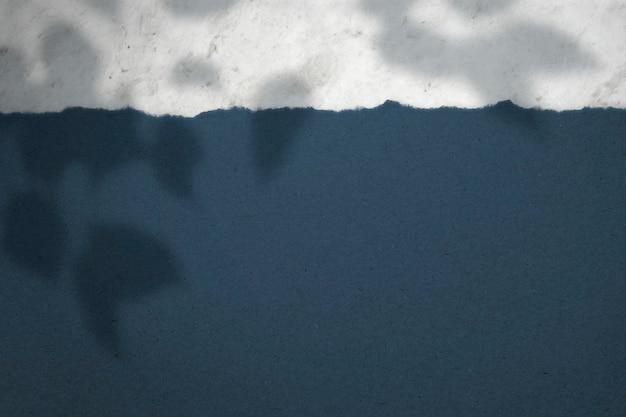 나뭇잎 배경의 그림자가 있는 회색 및 파란색 종이