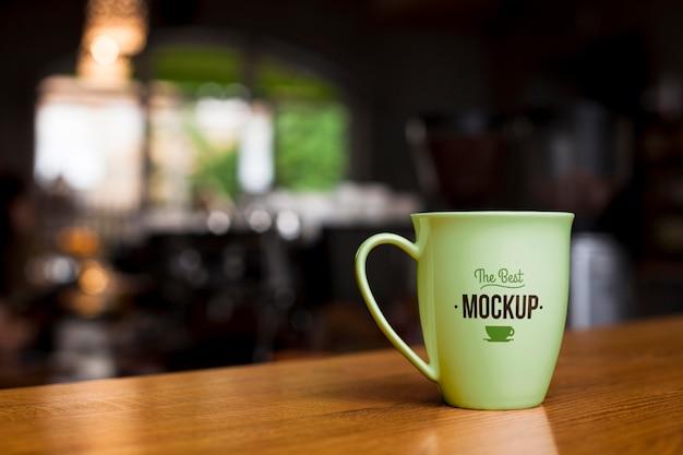木製のテーブルの上の緑のコーヒーカップ
