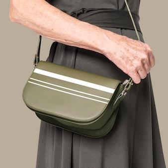 Psd макет зеленой сумки через плечо с полосатой женской одеждой