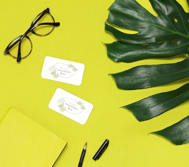 Green leaf of palm, glasses and notes on yellow background
