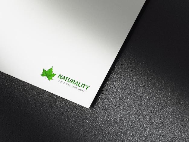 黒の背景を持つ白い紙に緑のロゴのモックアッププレミアムpsd