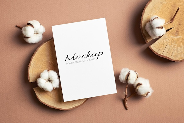Greeting card, flyer or invitation stationary mockup with wooden cut log and cotton flowers