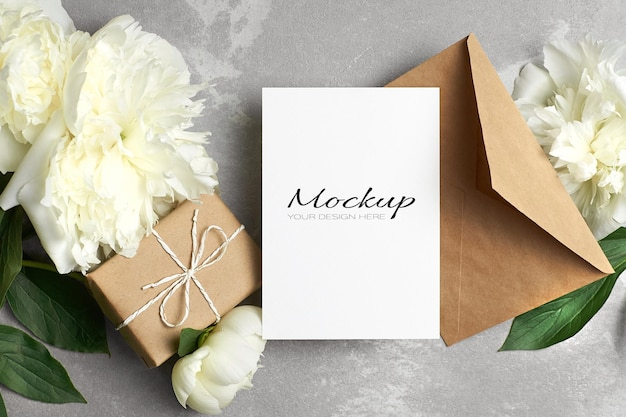 Greeting card or invitation mockup with envelope, gift box and white peony flowers on grey