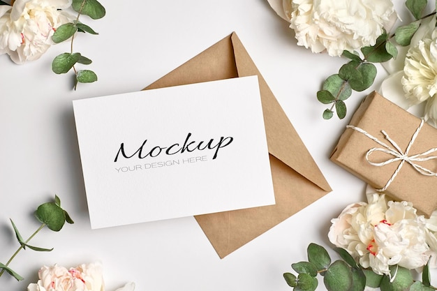 Greeting card or invitation mockup with envelope, gift box and white peony flowers with eucalyptus twigs