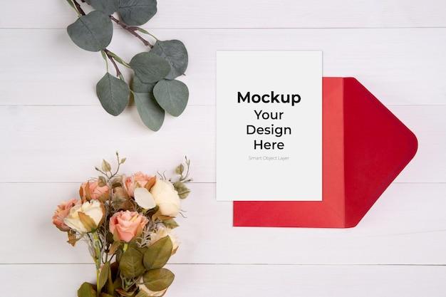 木製のテーブルにグリーティングカードのモックアップと花