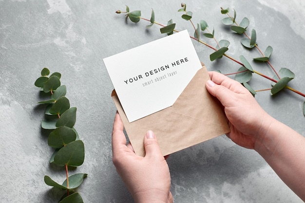 Greeting card mockup in female hands with eucalyptus twigs over grey