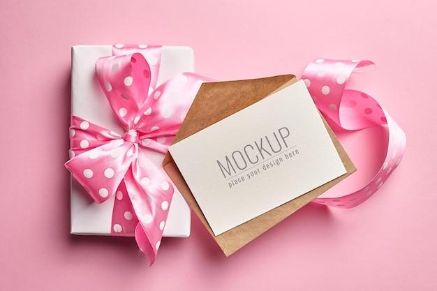분홍색 종이 표면에 활과 큰 선물 상자가있는 인사말 카드 모형