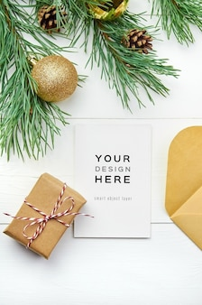Greeting card mockup with christmas decorations on white wooden background