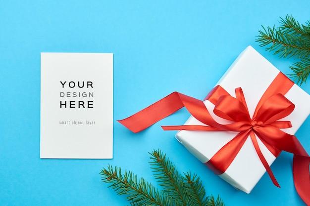 クリスマスギフトボックスとモミの木の枝のグリーティングカードのモックアップ
