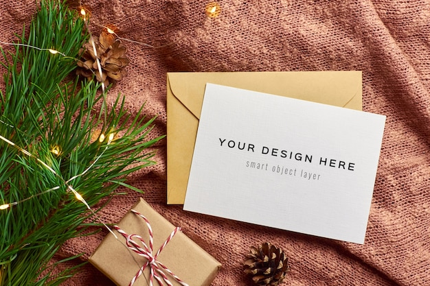 Greeting card mockup with christmas gift box, garland and pine tree branch