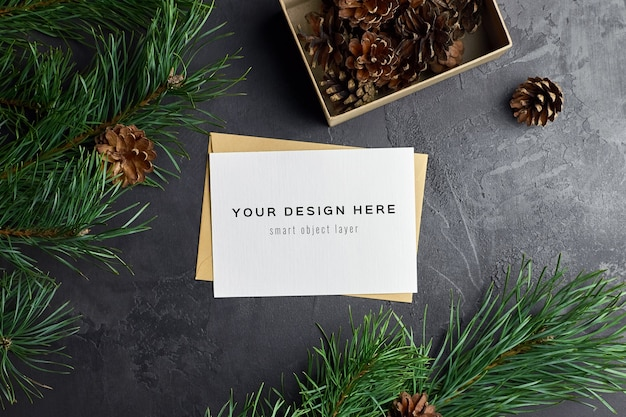 Greeting card mockup with christmas gift boxes and pine branches and cones on dark