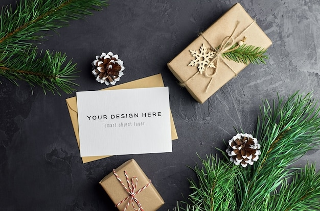 Greeting card mockup with christmas gift boxes and pine branches and cones