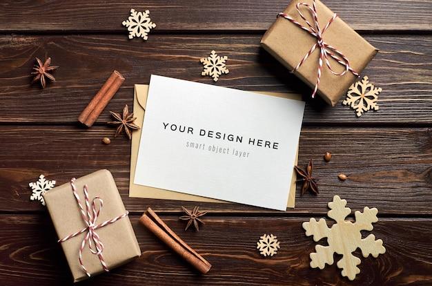 クリスマスギフトボックス、木製の装飾、暗いテーブルの上のスパイスとグリーティングカードのモックアップ