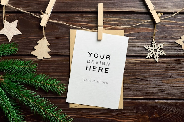 Greeting card mockup with christmas wooden decorations and fir tree branches