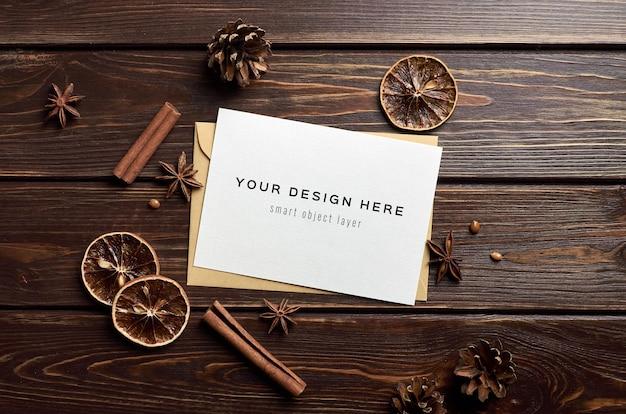 木製のテーブルにドライオレンジ、アニスの星、シナモンスティックのグリーティングカードのモックアップ