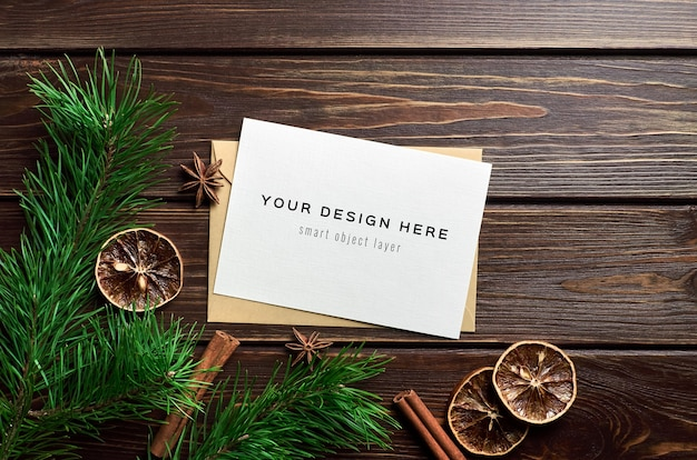 Greeting card mockup with dry oranges, spices and pine branches on wooden table