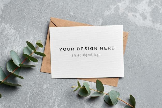 Макет поздравительной открытки с конвертом и ветками эвкалипта на сером