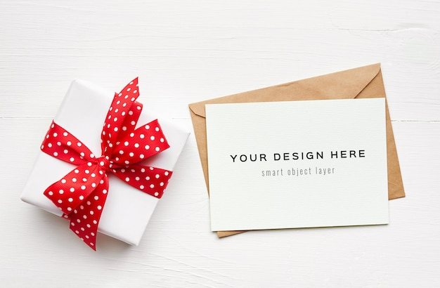 白いテーブルに赤いリボンの封筒とギフトボックスとグリーティングカードのモックアップ