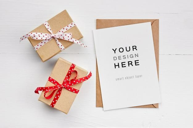 Макет поздравительной открытки с конвертом и подарочными коробками на белом деревянном фоне