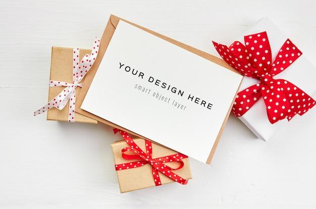 흰색 나무 배경에 봉투 및 선물 상자 인사말 카드 모형