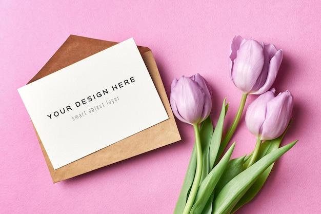 封筒と紫色のチューリップの花のグリーティングカードのモックアップ