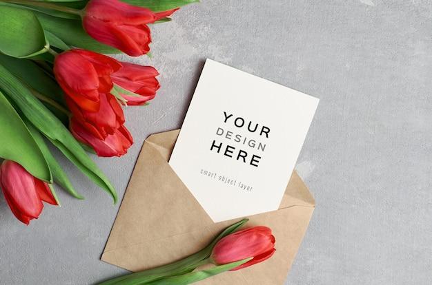 Макет поздравительной открытки с конвертом и букетом красных тюльпанов
