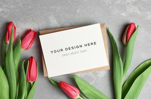 Макет поздравительной открытки с конвертом и цветами красных тюльпанов