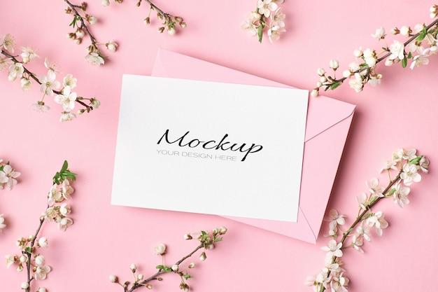 Макет поздравительной открытки с конвертом и ветками весеннего дерева с цветами