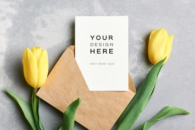 Макет поздравительной открытки с конвертом и цветами желтого тюльпана на сером