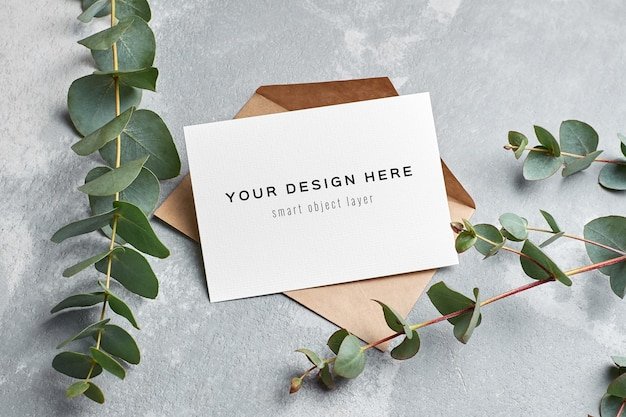Greeting card mockup with envelope and eucalyptus twigs on grey