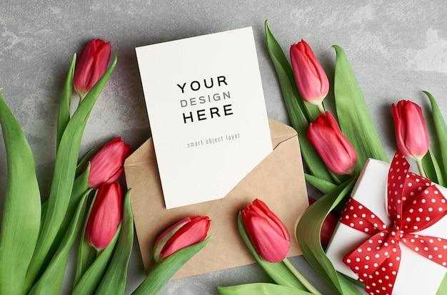 Макет поздравительной открытки с конвертом, подарочной коробкой и цветами красных тюльпанов