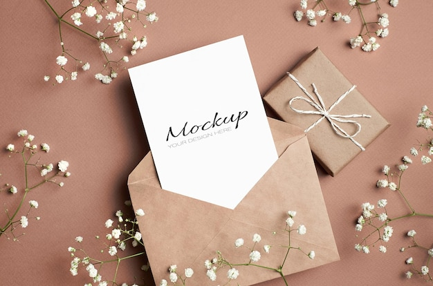 Greeting card mockup with envelope, gift box and white hypsophila flowers