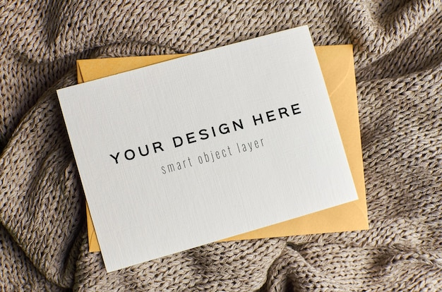 Greeting card mockup with envelope on knitted background