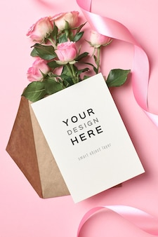 Greeting card mockup with envelope, pink ribbon and roses flowers bouquet