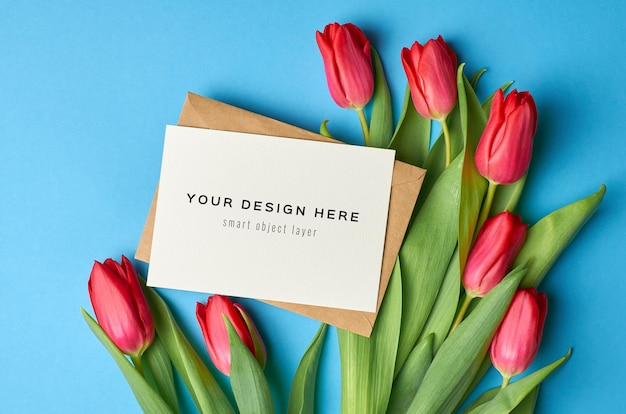 Greeting card mockup with envelope and red tulip flowers bouquet on blue background