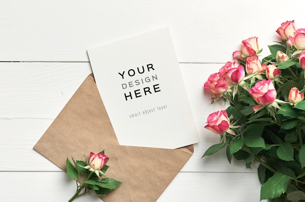Greeting card mockup with envelope and roses flowers on white wooden background