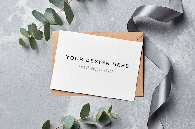 Greeting card mockup with envelope, silver ribbon and eucalyptus twig on grey