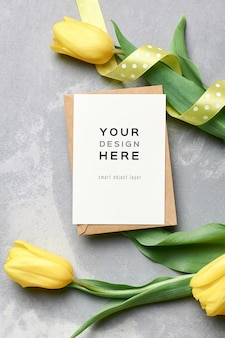 Greeting card mockup with envelope and yellow tulip flowers on grey