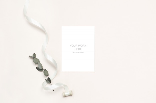 Greeting card mockup with eucalyptus branch and ribbon