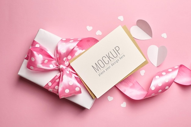 분홍색 표면에 선물 상자와 종이 마음으로 인사말 카드 모형
