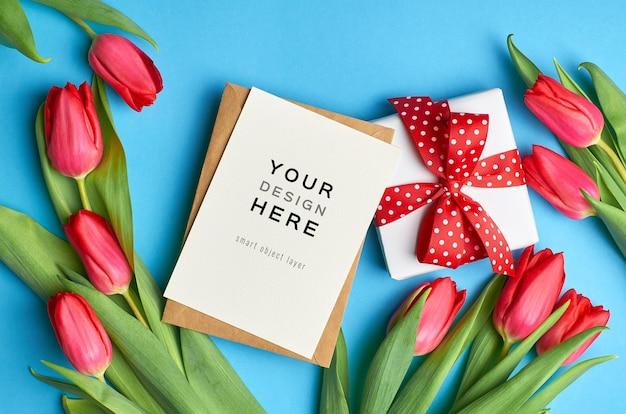 Макет поздравительной открытки с подарочной коробкой и цветами красных тюльпанов