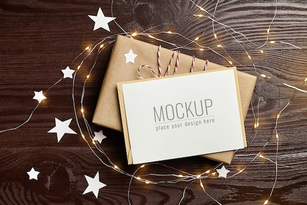 Greeting card mockup with gift box and christmas lights on wooden table