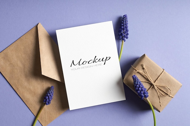 Greeting card mockup with gift box, envelope and blue muscari flowers