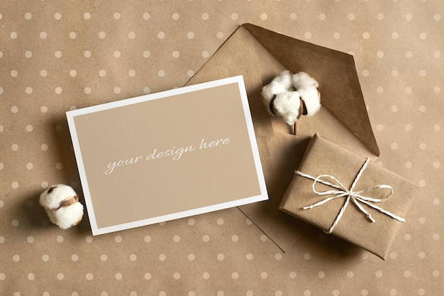 Greeting card mockup with gift box, envelope and cotton flowers