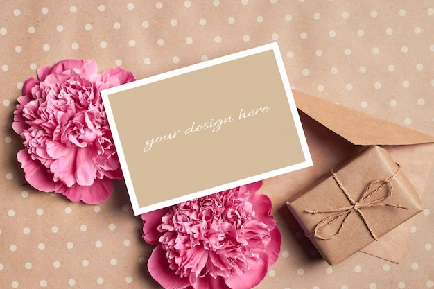 Greeting card mockup with gift box, envelope and pink peony flowers