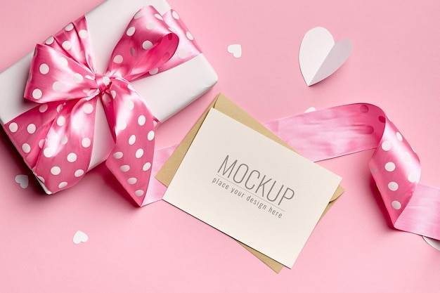 Greeting card mockup with gift box and paper hearts background
