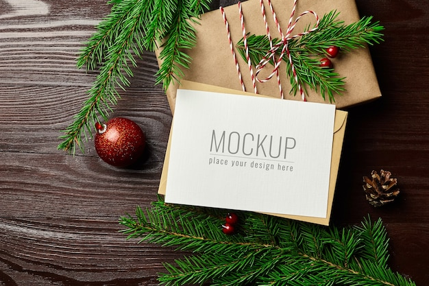 Greeting card mockup with gift box, red christmas ball and fir tree branches on wooden background