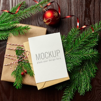 Greeting card mockup with gift box, red christmas ball and fir tree branches