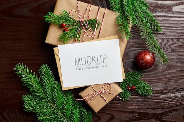 Макет поздравительной открытки с подарочной коробкой, красными елочными украшениями и еловыми ветками